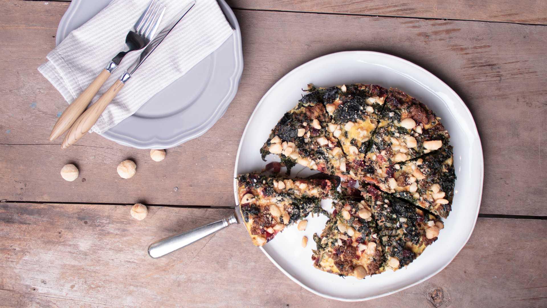 Eine bodenlose Gemüse-Hackfleisch-Quiche liegt angeschnitten auf einem Teller