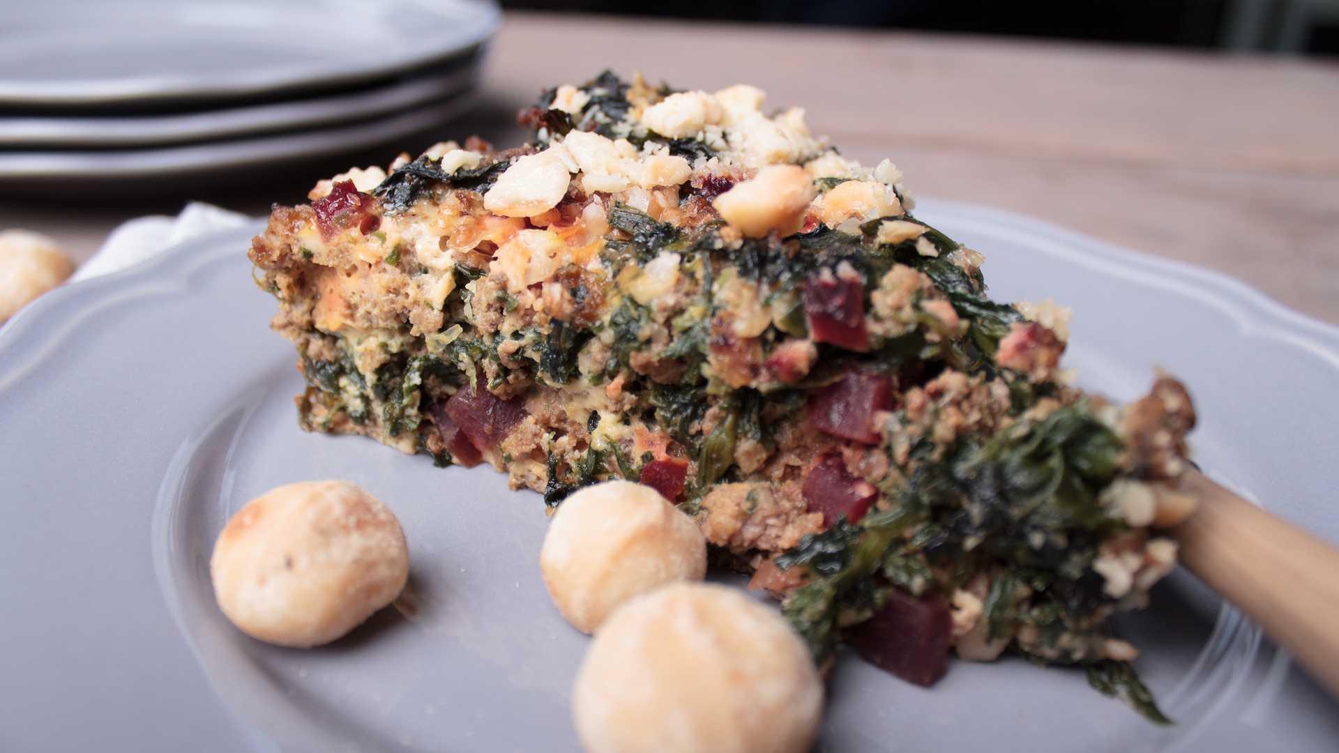 Auf einem Teller liegt ein Stück bodenlose Gemüse-Hackfleisch-Quiche