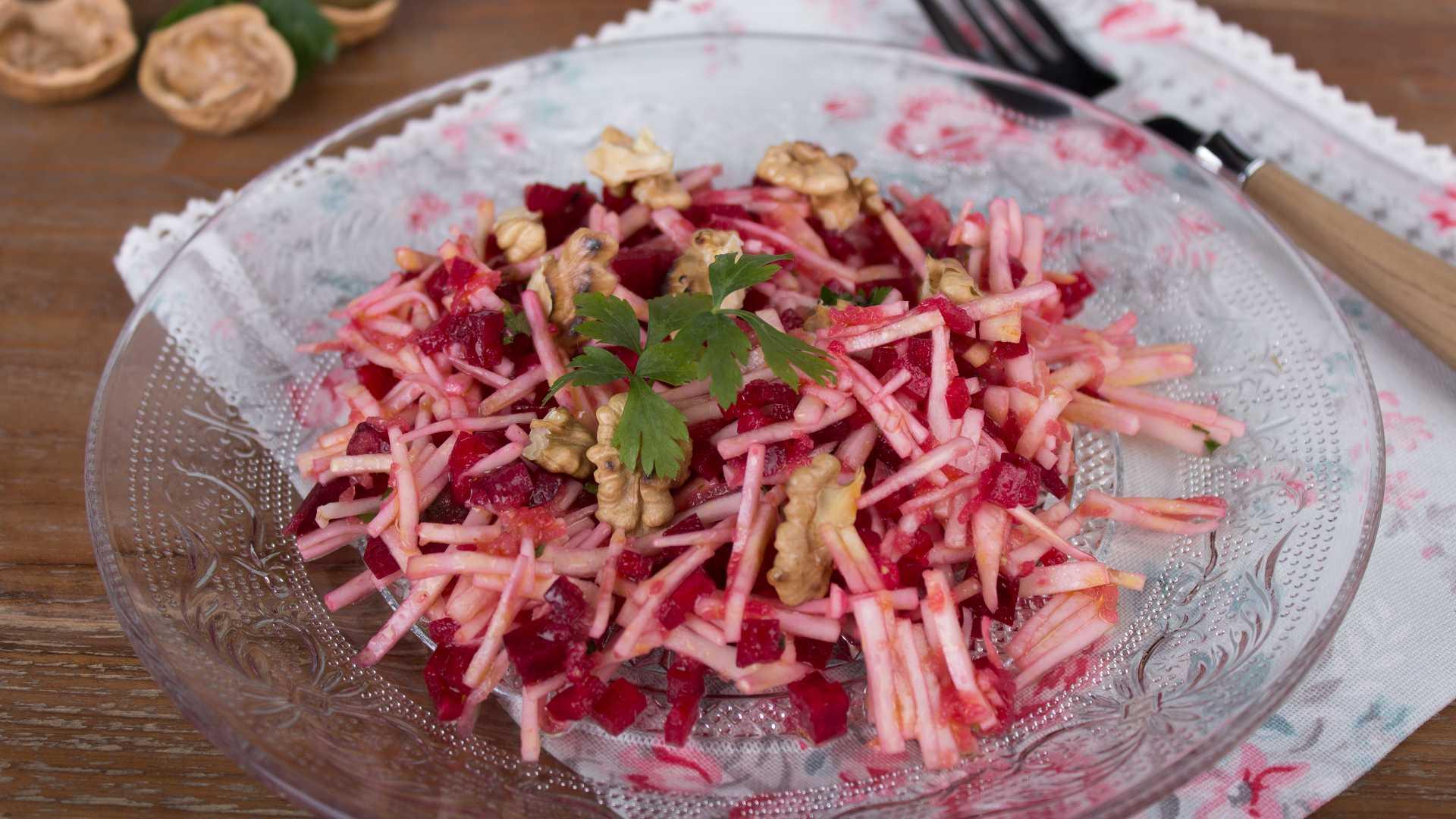 Auf einem Glasteller ist ein Wintersalat mit Sellerie und Rote Bete angerichtet