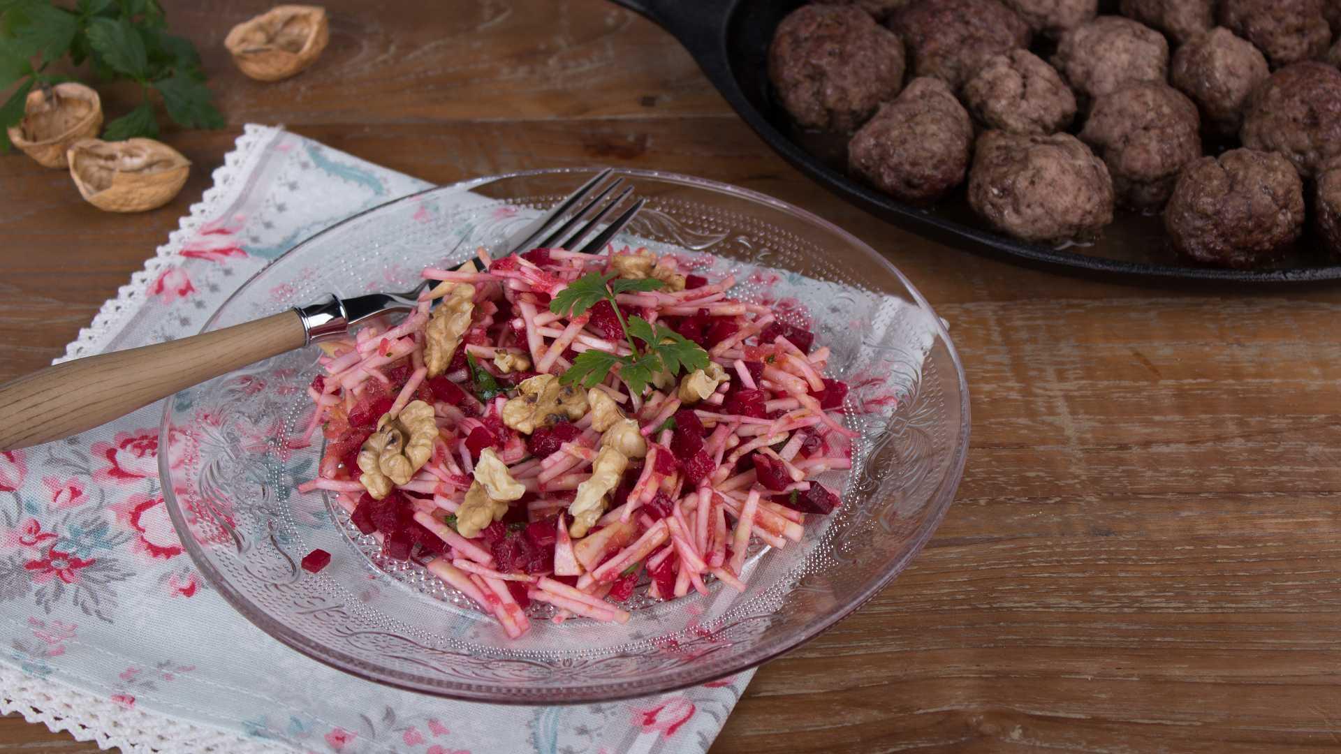 Auf einem Glasteller ist ein Sellerie-Rote-Bete Salat angerichtet, im Hintergrund ist eine Pfanne mit Hackbällchen