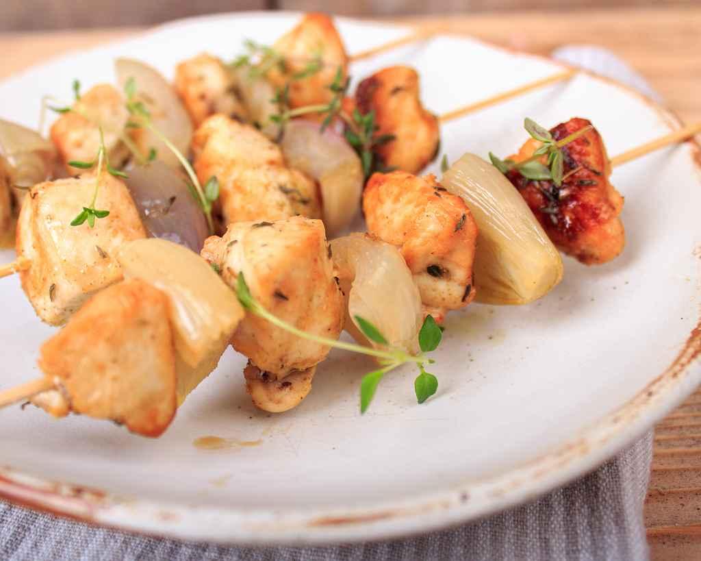 Gefluegel-Schalotten-Spiesse auf einem Teller